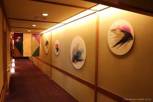 温泉旅館壁面に設置した、円形の和紙インテリアアートパネル(斜めから)